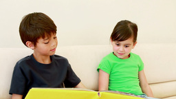 Happy siblings reading a book Footage