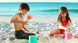 Siblings building sand castles Footage