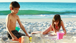 Smiling siblings building sand castles Footage