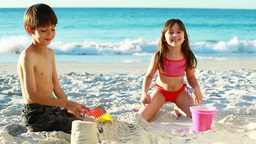 Smiling siblings building sand castles Stock Video Footage