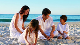 Cheerful family sitting on the sand Stock Video Footage