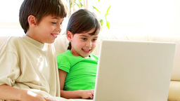 Siblings using a laptop together Stock Video Footage
