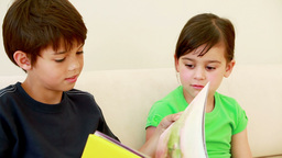 Brother and sister reading a book Footage