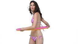 Woman in a pink bikini using a hula hoop Stock Video Footage
