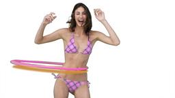 Woman in a pink bikini using a hula hoop Footage