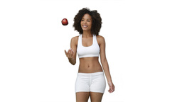 Woman in training clothes throws an apple upwards Stock Video Footage