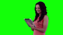 Woman using a tablet before looking at the camera Footage