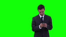 Businessman typing on his phone while looking arou Footage