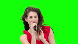 Woman gestures while singing into a microphone Footage