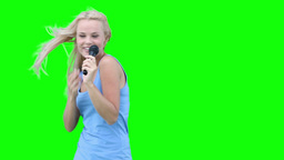 Blonde woman singing into a microphone Footage