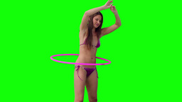Woman spinning a hula hoop with her arms raised ov Footage