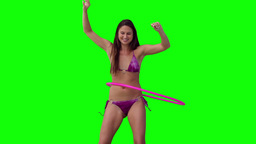 Woman spinning a hula hoop with her arms raised Stock Video Footage