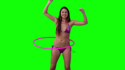 Woman spinning a hula hoop with her arms raised Footage