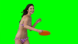 A woman catching and throwing a Frisbee Footage