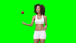 A woman walking and throwing an apple up and down Footage