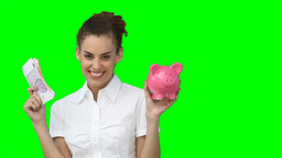 A woman with money and a piggybank in her hands Footage