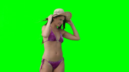 A woman in her bikini trying to hold on to her hat Footage
