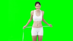 A woman uses a measuring tape to check her waist l Stock Video Footage