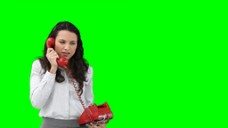 A business woman talking to someone on a red telep Footage