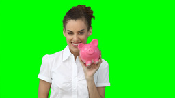 A woman holding up a piggybank and a fan of cash a Footage