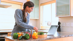 Woman cooking while looking at the recipe Stock Video Footage