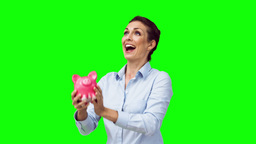 Happy woman in slow motion throwing a piggy bank Footage