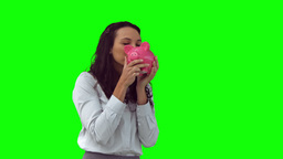 Happy woman in slow motion holding a piggy bank Footage