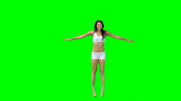 Dark haired woman jumping into the shape of an x Footage