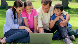 Smiling family looking at a laptop together Footage