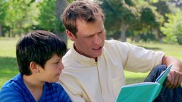 Father and son reading a book aloud Stock Video Footage
