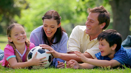 Smiling family trying to catch a soccer ball Stock Video Footage