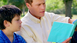 Father and son reading a fascinating book Footage