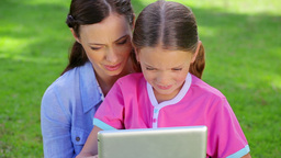 Smiling mother and daughter using a tablet compute Footage