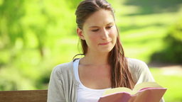Woman reading a book while sitting on a bench Footage