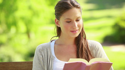 Woman reading a book while sitting on a bench Stock Video Footage