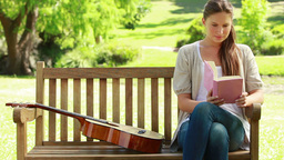 Woman sitting on a bench is reading a book Footage