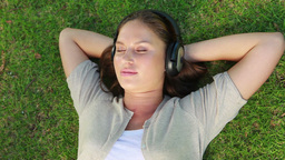 Woman lying on the grass with headphone on Stock Video Footage