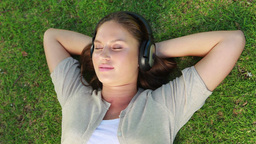 Woman lying on the grass with headphone on Footage