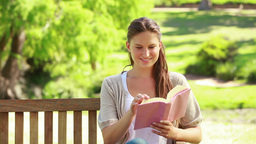 Woman reading a novel in a park Footage