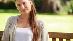 Smiling young woman sitting on a bench Stock Video Footage