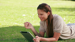 Woman using an eBook in a park Stock Video Footage