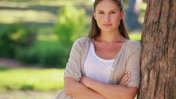 Young woman leaning against a tree Stock Video Footage