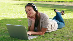 Woman listening to music with a laptop in front of Footage