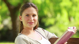 A woman is reading a book on a bench Stock Video Footage