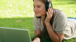 Woman wearing headphones while using a laptop Footage
