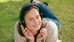 Woman lying on her front listening to music Footage
