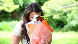 Smiling brunette holding a bunch of flowers Footage