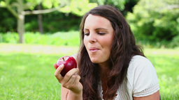 Smiling brunette haired woman eating a red apple Footage