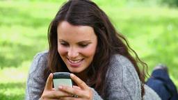 Smiling brunette woman sending a text message Footage