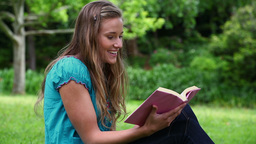Smiling young woman reading a novel Footage